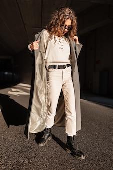 Jong mooi meisje met krullend haar in modieuze kleding met een vintage jas, zonnebril, trui, broek en laarzen loopt in de stad op een zonnige dag