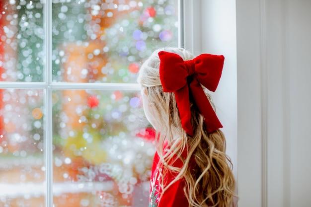 Jong mooi meisje met lang blond krullend haar met kerst rode boog en winter trui zittend op het grote raam met sneeuwende achtergrond.