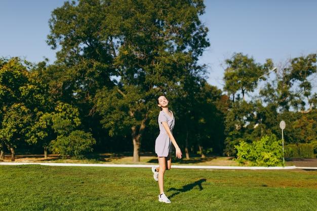 Jong mooi meisje met lang bruin haar gekleed in lichte kleding die op groen gazongras in het park op bomenachtergrond blijft. zomer zonnige tijd.