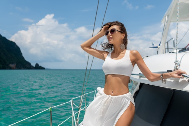 Jong mooi meisje met lang haar dat zich op de boog van het jacht in witte rok en bikini bevindt.