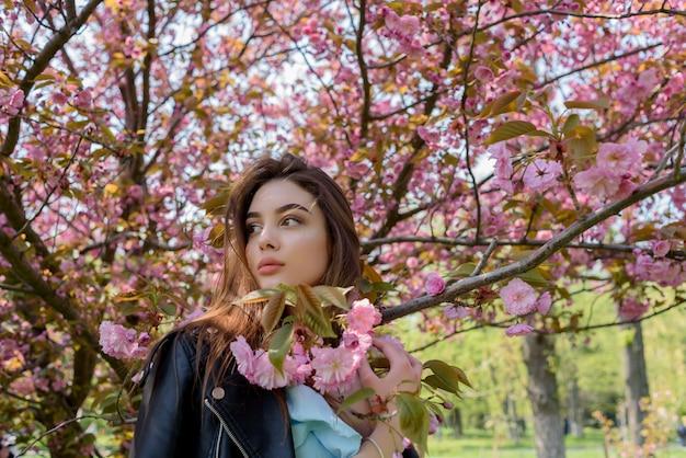 Jong mooi meisje met lang haar geniet van de schoonheid van de lente natuur in de buurt van de bloei blossom