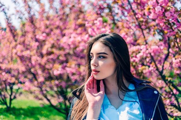 Jong mooi meisje met lang haar geniet van de schoonheid van de lentenatuur in de buurt van de bloeiende sakura-boom