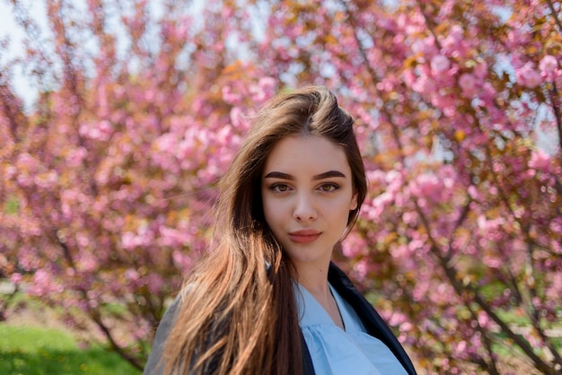 Jong mooi meisje met lang haar geniet van de schoonheid van de lentenatuur in de buurt van de bloeiende sakura