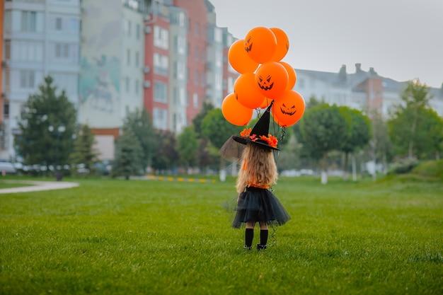Jong mooi meisje met lang haar in kostuum als een kleine heks die zich op groene open plek in het park met pompoenballons bevindt. uitzicht vanaf de achterkant. vakantieconcept.