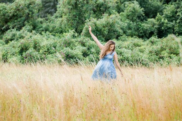 Jong mooi meisje met mooi lang haar in een blauwe jurk loopt over het veld