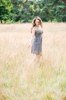 Jong mooi meisje met mooi lang haar in een grijze jurk loopt over het veld