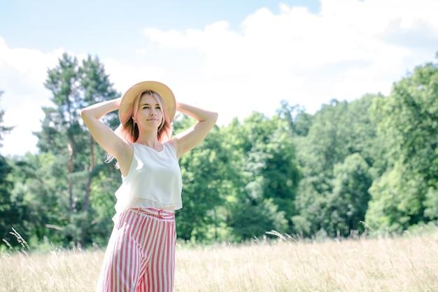 Jong mooi meisje met roze haar in de zomerhoed op de open plek