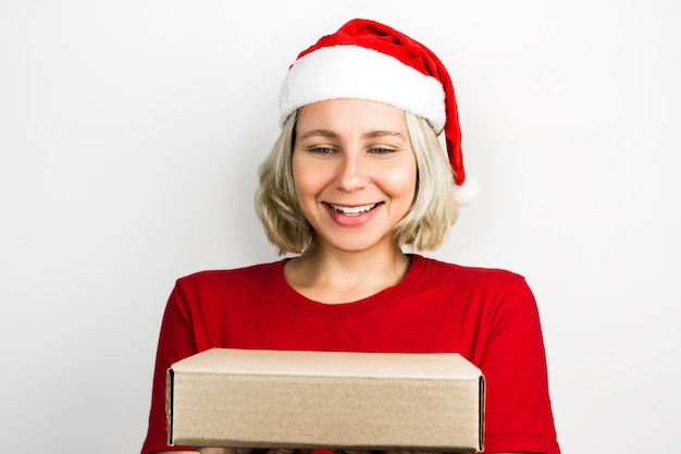 Jong mooi meisje met santa claus accessoires zoals santa's cap en rode outfit geïsoleerd op een witte achtergrond. foto voor kerstmis. braziliaans, kaukasisch, blond haar, groene ogen.