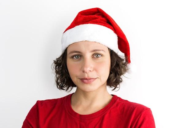 Jong mooi meisje met santa claus accessoires zoals santa's cap en rode outfit geïsoleerd op een witte achtergrond. foto voor kerstmis. braziliaans, kaukasisch, zwart haar, groene ogen.
