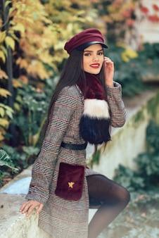 Jong mooi meisje met zeer lang haar die de winterlaag en glb in de herfstbladeren dragen