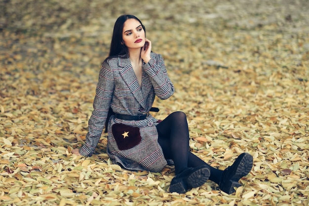 Jong mooi meisje met zeer lang haar die de zitting van de de winterlaag op de vloer van een stedelijk park dragen