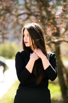 Jong mooi meisje poseren in een zwart leren jas in het park