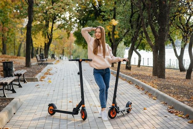 Jong mooi meisje rijden in het park op elektrische scooters op een warme herfstdag.