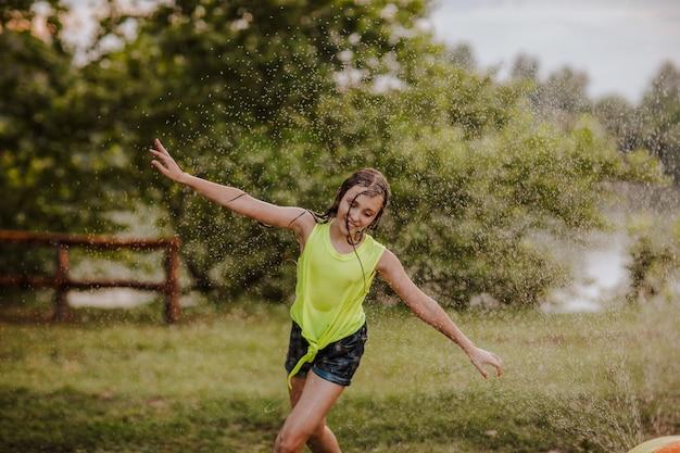 Jong mooi meisje spelen met water spatten