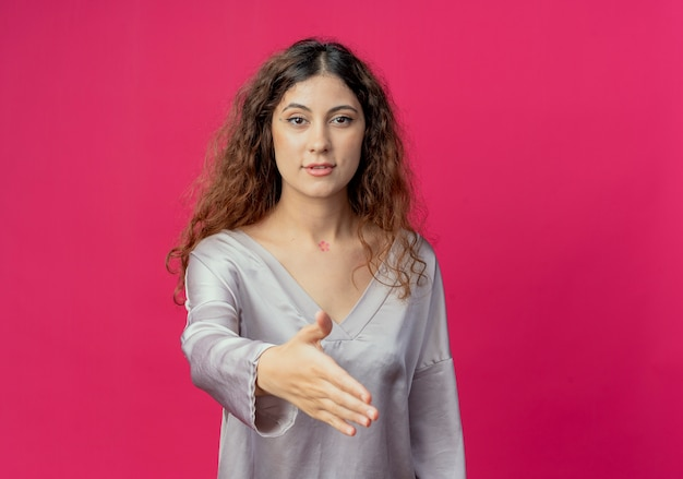 Jong mooi meisje stak hand geïsoleerd op roze muur