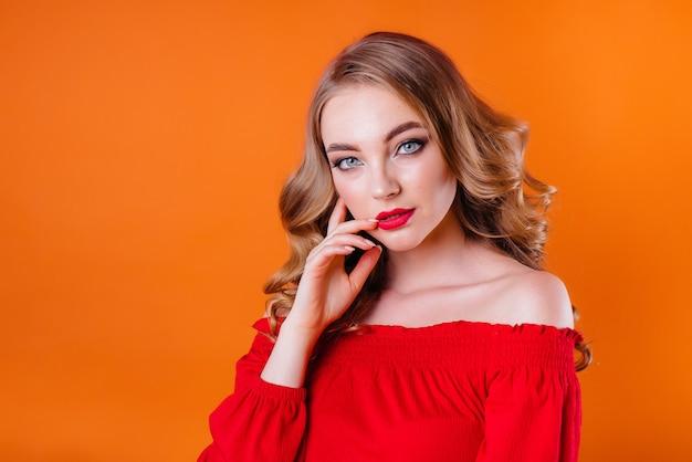 Jong mooi meisje toont emoties en glimlacht op een sinaasappel.