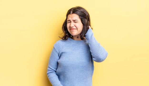Jong mooi meisje voelt zich gestrest, gefrustreerd en moe, wrijft over pijnlijke nek, met een bezorgde, verontruste blik