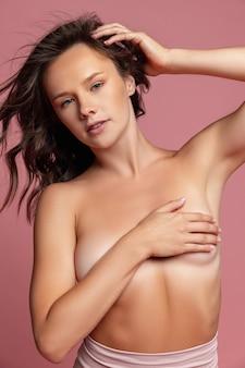 Jong mooi meisje vrouwelijk naakt model geïsoleerd over roze studio muur natuurlijke schoonheid