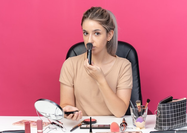 Jong mooi meisje zit aan tafel met make-up tools die poeder blush toepassen geïsoleerd op roze muur