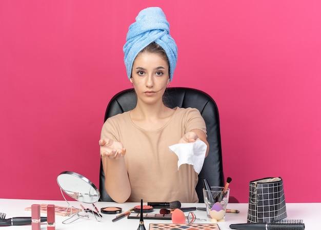 Jong mooi meisje zit aan tafel met make-uptools gewikkeld haar in een handdoek en steekt servet uit dat op roze muur is geïsoleerd