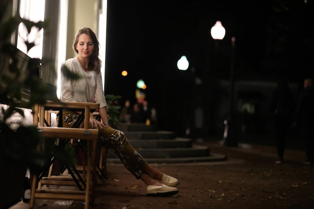 Jong mooi meisje zit 's nachts in een straatcafé