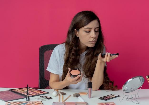 Jong mooi meisje, zittend aan de make-up tafel met make-up tools die poeder houden en blozen kijken naar poeder geïsoleerd op een karmozijnrode achtergrond
