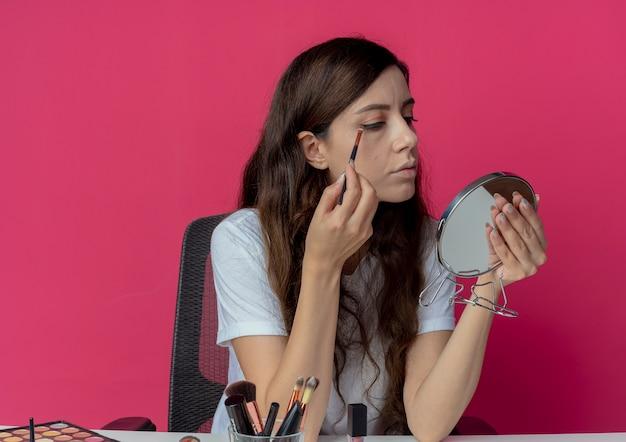 Jong mooi meisje, zittend aan de make-up tafel met make-up tools houden en kijken naar spiegel toepassing van oogschaduw geïsoleerd op crimson achtergrond