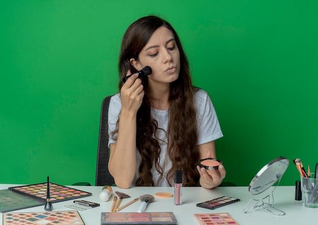 Jong mooi meisje zittend aan make-up tafel met make-up tools houden en kijken naar blozen en toepassen op gezicht geïsoleerd op groene achtergrond