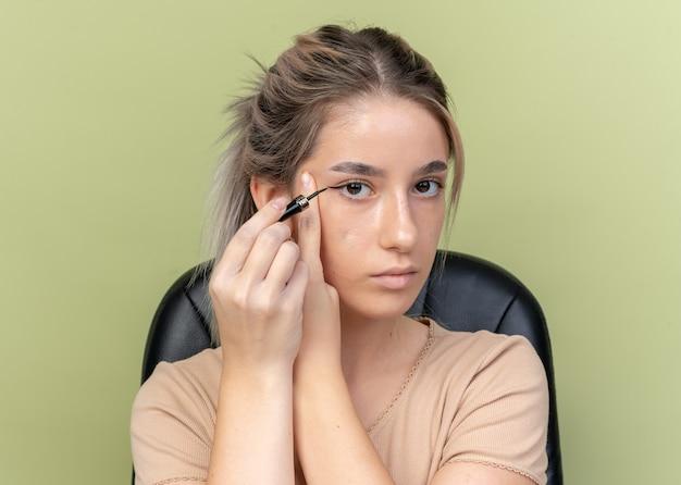 Jong mooi meisje zittend aan tafel met make-up tools teken pijl met eyeliner geïsoleerd op olijfgroene muur