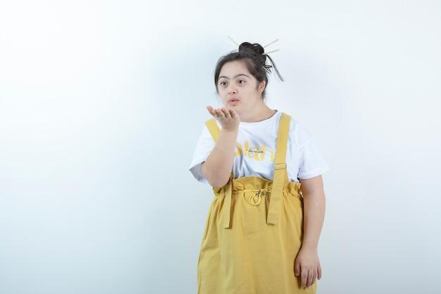 Jong mooi meisjesmodel dat en een luchtkus bevindt zich tegen witte muur blaast.