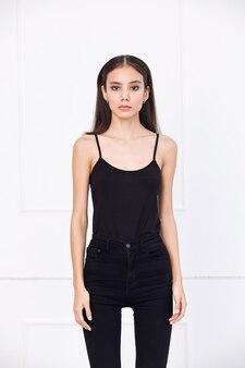 Jong mooi model met natuurlijke make-up en mooi haar op een witte achtergrond in zwarte jeans