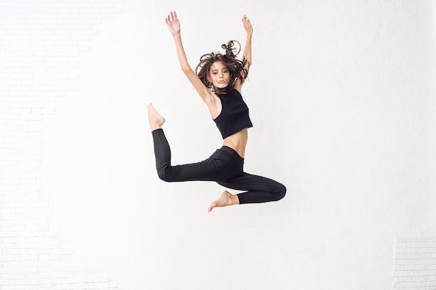 Jong mooi model springt hoog met natuurlijke make-up en mooi haar op een witte achtergrond