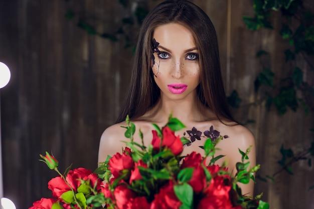 Jong mooi mooi meisje die en doos met rode rozen bevinden zich houden. vogue-het portretmeisje van de manierstijl in zwarte elegante kleding status
