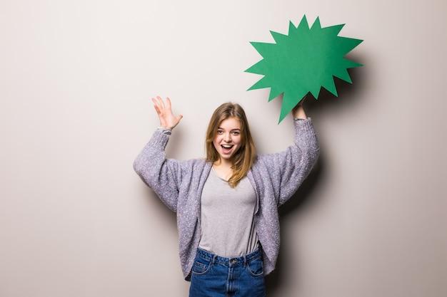 Jong mooi opgewonden tienermeisje dat een groene geïsoleerde bel voor tekst houdt
