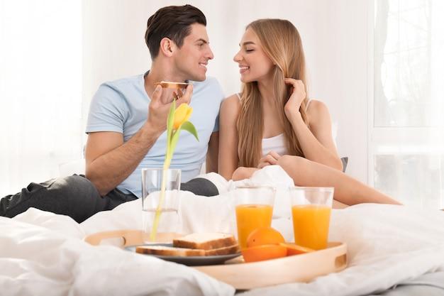 Jong mooi paar dat ontbijt op bed heeft