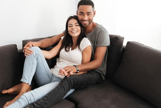Jong mooi paar dat op een bank thuis lacht. voorkant kijken.