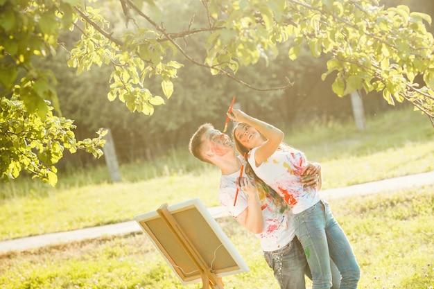 Jong mooi paar dat pret in openlucht met schilderijen heeft. knappe kerel die zijn vriendin omhelst en zij allebei lachen en genieten van. jongens glimlachen