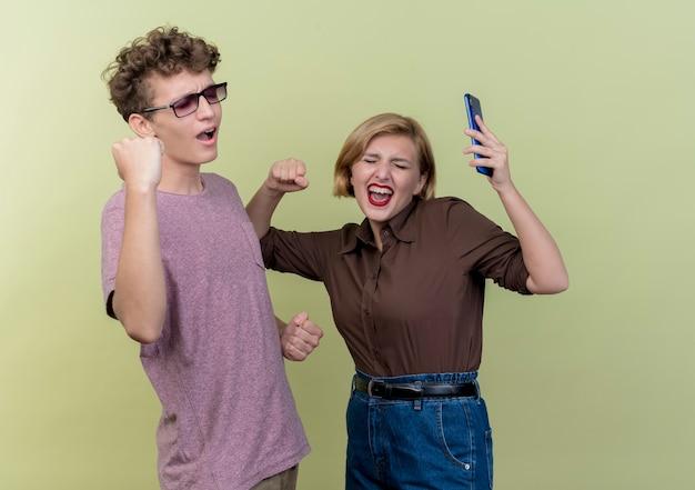 Jong mooi paar dat vrijetijdskleding draagt jongen en meisje balde vuisten blij en opgewonden staande over lichte muur