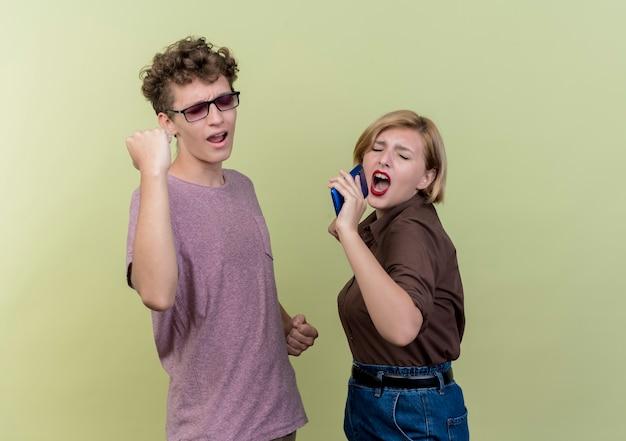 Jong mooi paar dat vrijetijdskleding draagt jongen en meisje blij en opgewonden plezier hebben gelukkig samen staande over lichte muur