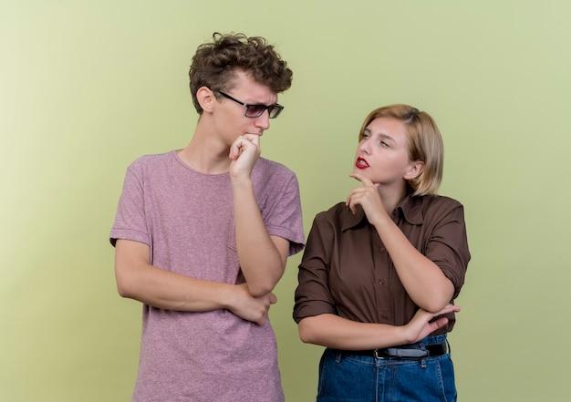 Jong mooi paar dat vrijetijdskleding draagt jongen en meisje die elkaar met peinzende uitdrukking bekijken die zich over lichte muur bevinden