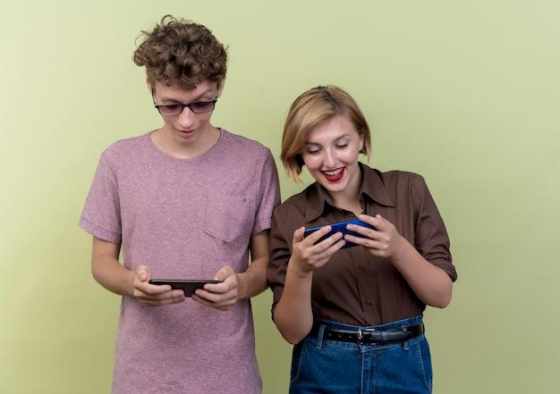 Jong mooi paar dat vrijetijdskleding draagt, jongen en meisje die smartphones het gelukkige en positieve glimlachen houden die zich over lichte muur bevinden