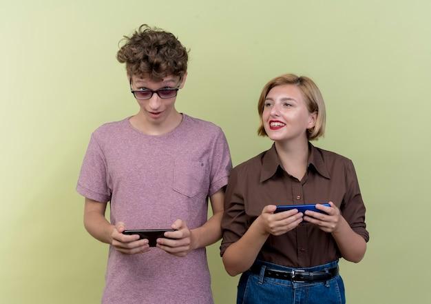 Jong mooi paar dat vrijetijdskleding draagt, jongen en meisje die smartphones het gelukkige en positieve glimlachen over licht houden