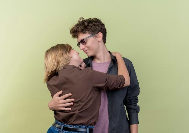 Jong mooi paar dat vrijetijdskledingjongen en meisje draagt die zich van aangezicht tot aangezicht gelukkig verliefd bevinden die over lichte muur koesteren
