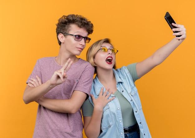 Jong mooi paar dat zich verenigt die mobiele telefoon gebruiken die selfie glimlachen die v-teken over oranje muur tonen