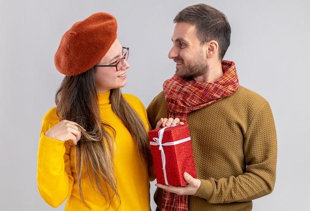 Jong mooi paar gelukkige man die een cadeau geeft voor zijn glimlachende vriendin in baret gelukkig verliefd samen vieren valentijnsdag staande over witte muur