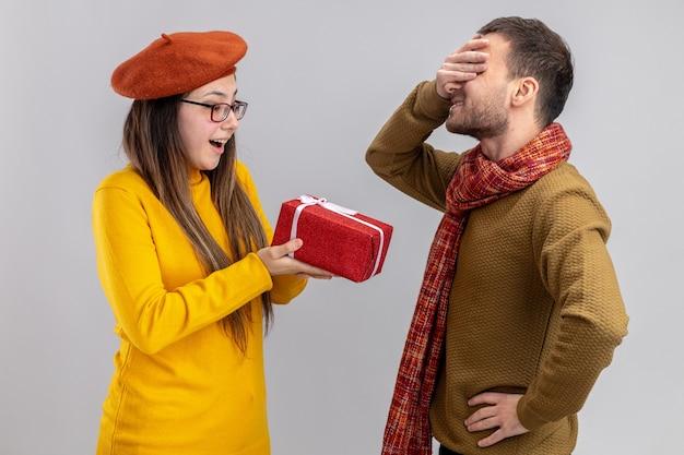 Jong mooi paar gelukkige vrouw in baret die een cadeau geeft voor haar vriend die de ogen bedekt met handen gelukkig verliefd samen valentijnsdag vieren staande over witte muur