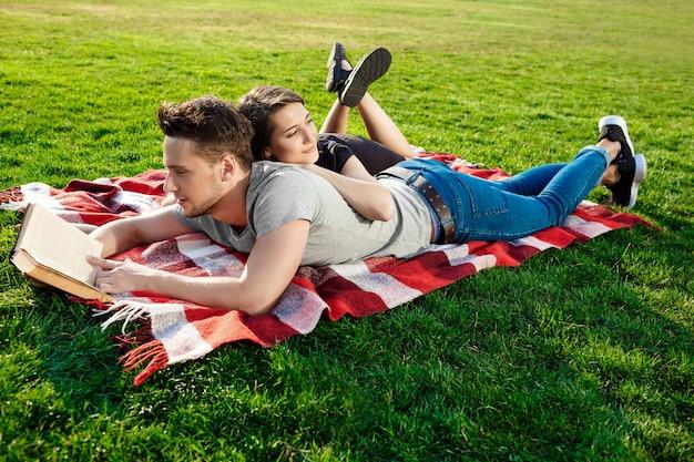 Jong mooi paar het glimlachen lezing bij park.