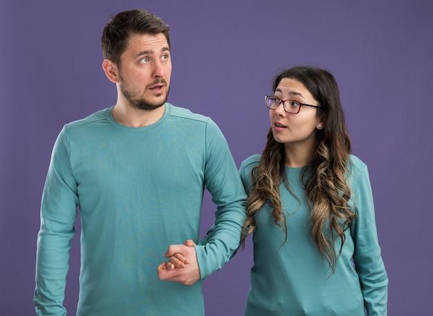 Jong mooi paar in blauwe vrijetijdskleding, gelukkige en vrolijke man en vrouw die gelukkig verliefd zijn, vieren valentijnsdag die over paarse muur staat