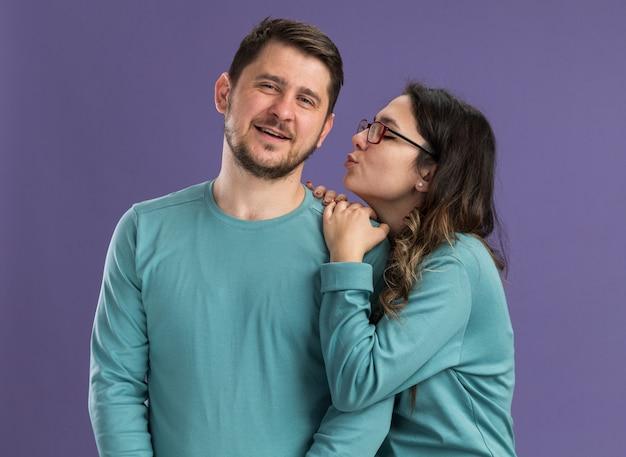 Jong mooi paar in blauwe vrijetijdskleding gelukkige vrouw die haar tevreden vriendje gaat kussen, gelukkig verliefd samen