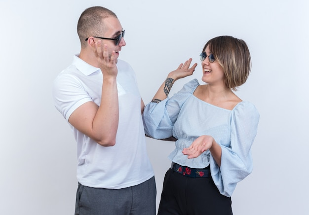 Jong mooi paar in vrijetijdskleding man en vrouw kijken elkaar gelukkig en vrolijk aan en nemen vijf staande